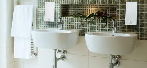 white sinks in bathroom with green tiling on wall and wave dispensers dispenser amenities