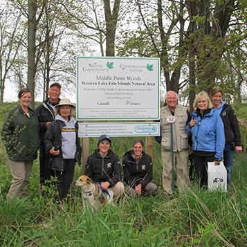 people dressed in outdoor wear standing beside middle point woods western lake erie islands national area sign dispenser amenities