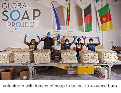 Volunteers with loaves of soap to be cut into 4 ounce bars dispenser amenities