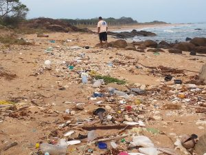 man walks along plastic beach