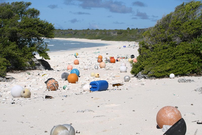 balls bottles and other plastic objects washed up on a beach dispenser amenities