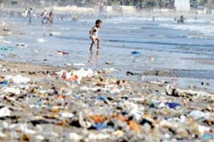 Child walks along trash filled beach in Sri Lanka