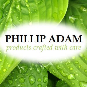 Phillip Adam products crafted with care background of leaves covered with dew dispenser amenities