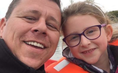 man and little girl in life jacket smiling at camera dispenser amenities