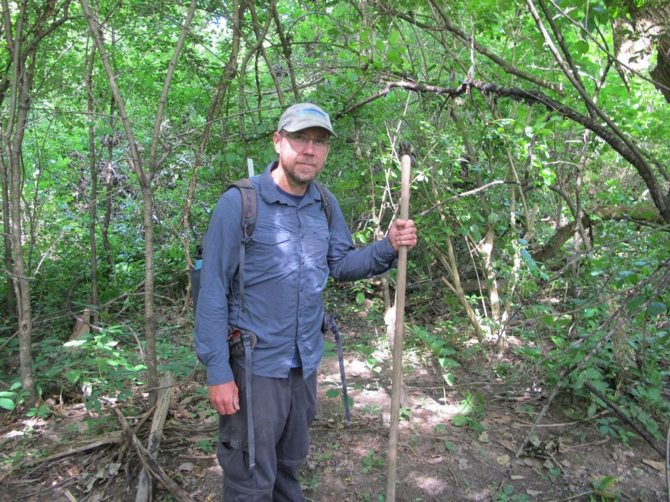 Man standing in woods holding wooden stick wearing backpack dispenser amenities